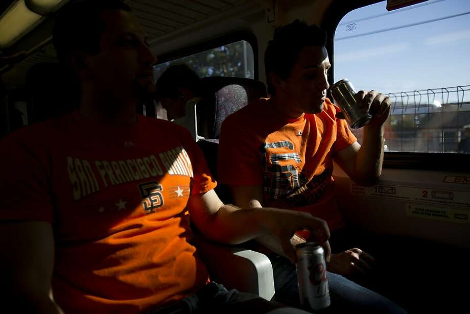 Daniel Costa (left) and friend James Conti enjoy beers on the ride up to a recent Giants game aboard Caltrain. Photo: Stephen Lam, Special To The Chronicle