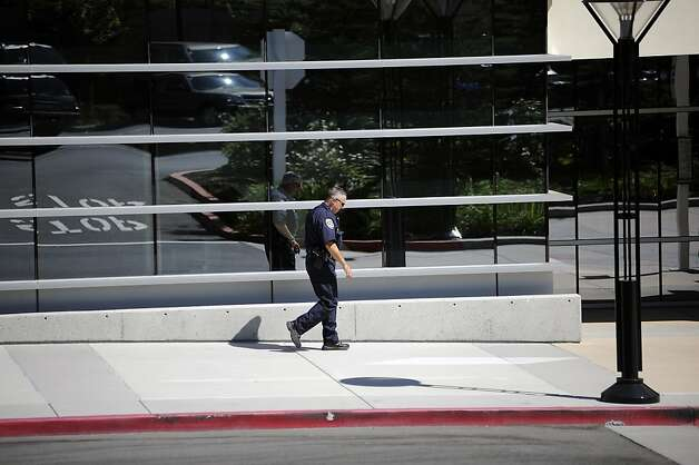 A lone police officer walks in front of the hospital.  CHP officer and suspect who were shot during a shootout on 680 near Walnut Creek, have been taken to John Muir Medical Center in Walnut Creek.  Tuesday September 4th, 2012. Photo: Michael Short, Special To The Chronicle
