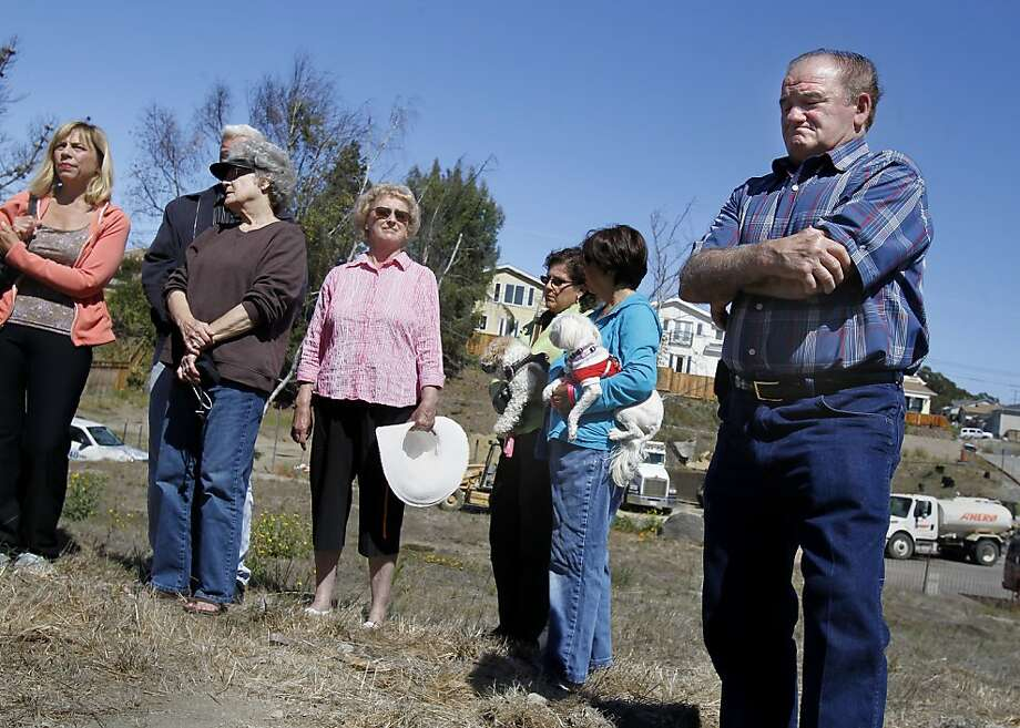 Jacques Chiramberro (right) and other neighbors stand just feet away from where the pipeline erupted two years ago. Chiramberro has rebuilt his home - after many hours of dealing with his insurance company and PG&E - but many other sites are either vacant or have work in progress. Photo: Brant Ward, The Chronicle