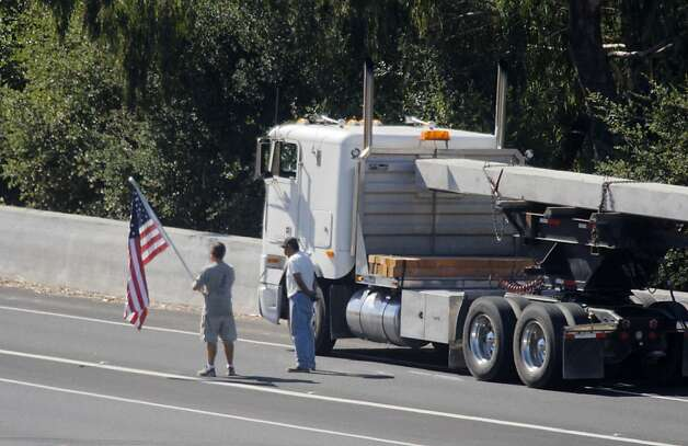 One man holds an American flag as he stands next to a truck stopped behind the scene of a shooting as he watches activity at the scene on Interstate 680 near Alamo, Calif. on Tuesday, September 4, 2012. A California Highway Patrol officer was conducting a traffic stop in the area when gunfire broke out. Photo: Lea Suzuki, The Chronicle