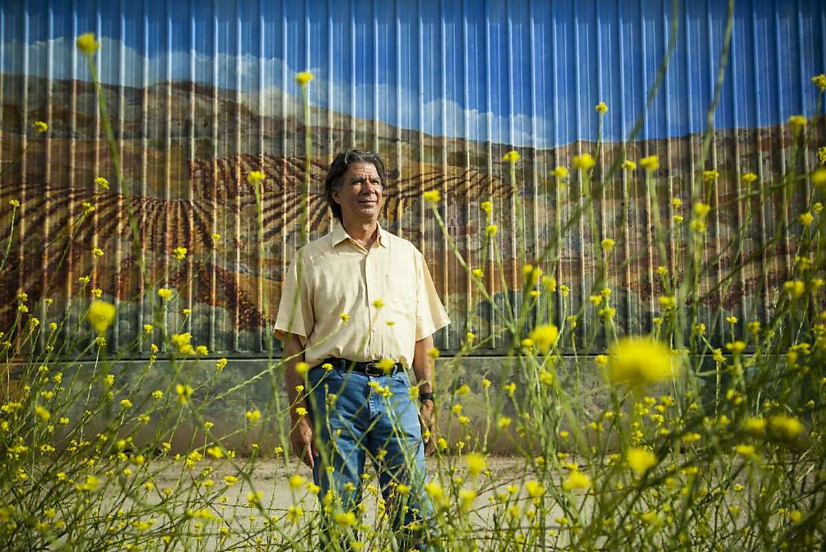 winemonth09_santabarbara September 1, 2012: Lompoc, California Richard Longoria, winemaker and owner of Longoria Wines, a small family owned winery, established in 1982. Richard Longoria stands in front of mural painted on the side of an industrial building in the Lompoc Wine Ghetto, a unique two-block industrial complex which has been almost completely taken over by the wine industry. The city of Lompoc, located in Santa Barbara County is dubbed