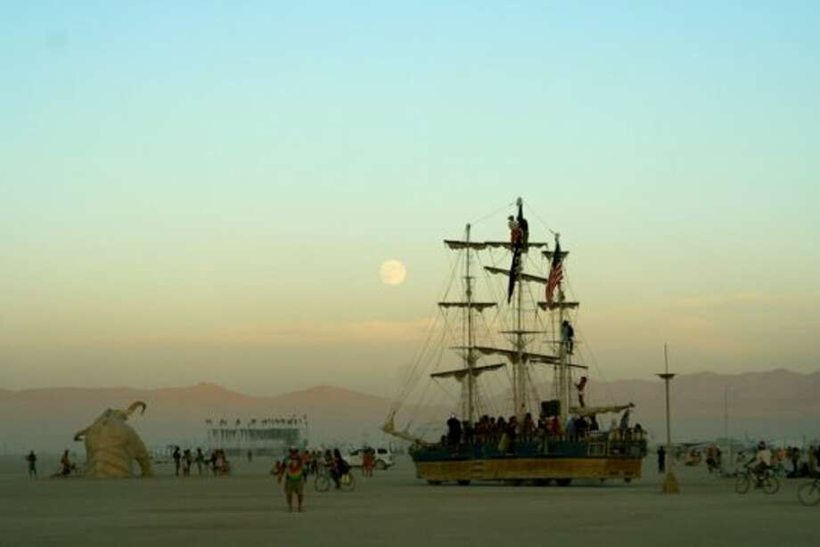 My fave time of day: right around sundown, the air still incredibly warm, the playa calm and mellow as the boats go cruising by under a full and pregnant moon before everyone heads to their camps to eat and prepare to come back out and cruise/party/dance/ogle the moon all night.