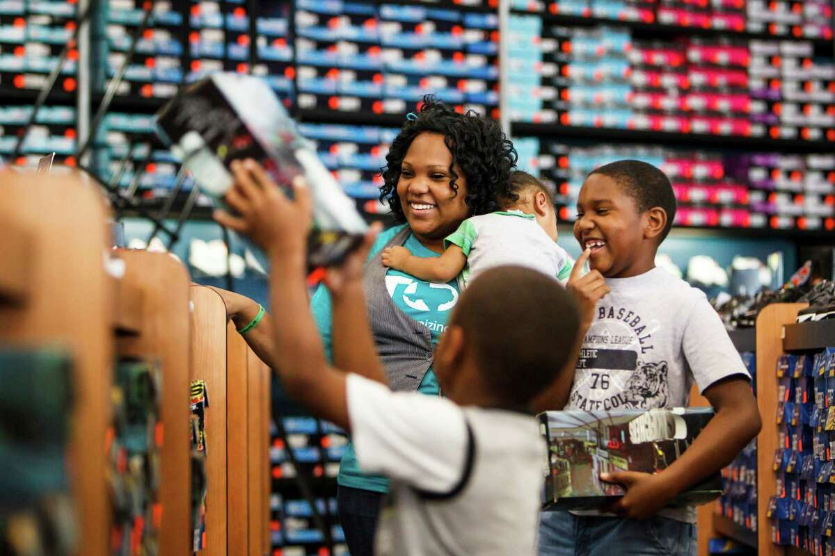 Single mother of three Tameka Morris helps sons Tyler, 6, and Taylor, 9, shop for new shoes at an outlet store in Houston.