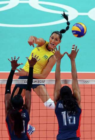Jaqueline Carvalho #8 of Brazil spikes the ball against Foluke Akinradewo #16 and Destinee Hooker #19 of United States during the Women's Volleyball gold medal match on Day 15 of the London 2012 Olympic Games at Earls Court on August 11, 2012 in London, England. Photo: Ezra Shaw, Getty Images / Getty Images Europe