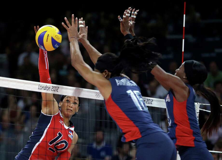 Dominican Republic's Milagros Cabral de la Cruz, left, spikes the ball past United States' Foluke Akinradewo, center, and Destinee Hooker during a women's quarterfinal volleyball match at the 2012 Summer Olympics, Tuesday, Aug. 7, 2012, in London. Photo: Jeff Roberson, Associated Press / AP