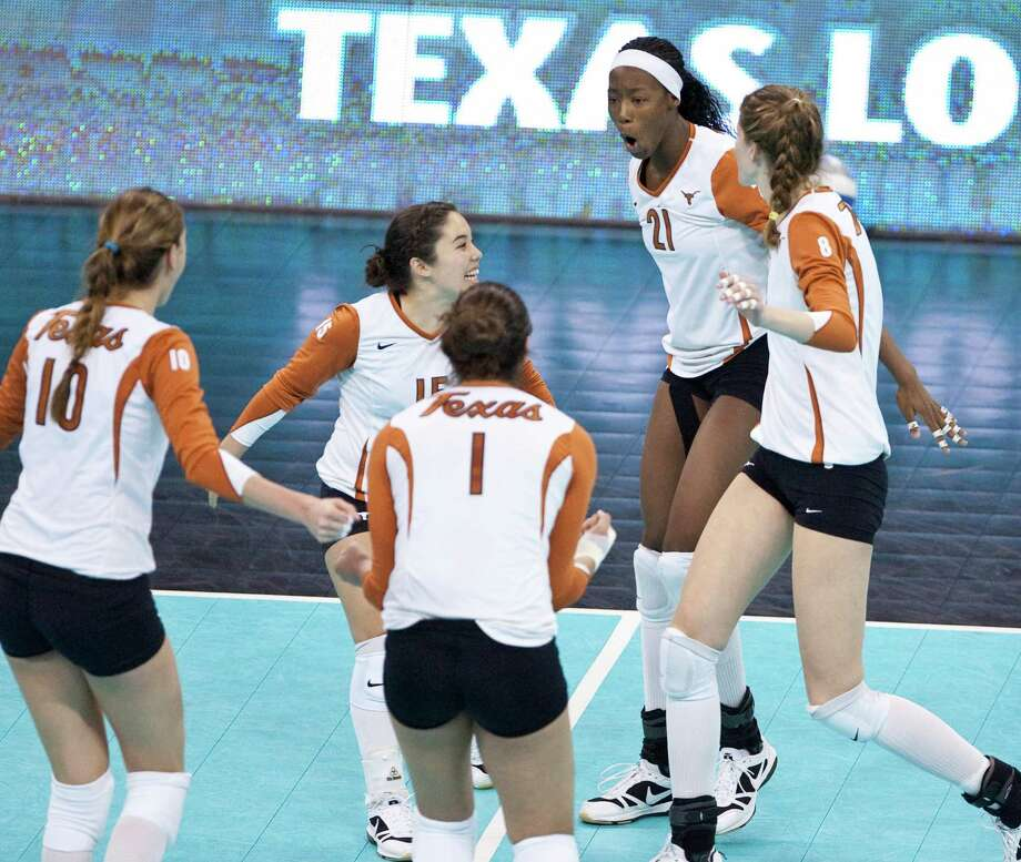 Texas players, including Juliann Faucette (1), Sydney Yogi (15) and Destinee Hooker (21) celebrate winning a point against Texas A&M in an NCAA college volleyball regional match, in Omaha, Neb., Friday, Dec. 11, 2009. Texas defeated Texas A&M 25-18, 25-18, 25-21. Photo: Nati Harnik, Associated Press / AP