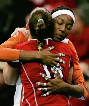 Texas' Destinee Hooker hugs Nebraska's Kori Cooper, with back to camera, following the NCAA college volleyball Omaha regional final match in Omaha, Neb., Saturday, Dec. 12, 2009. Texas beat Nebraska 21-25, 25-18, 25-16, 25-17. Photo: Nati Harnik, Associated Press / AP