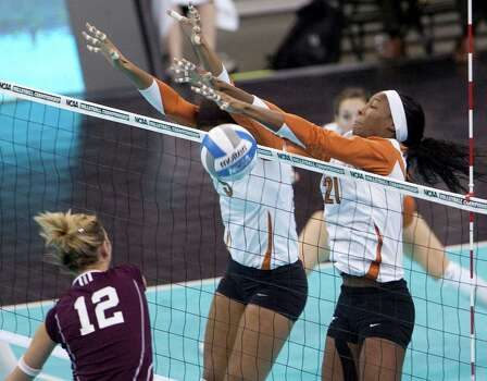 Texas' Destinee Hooker (21), and Rachael Adams (5) block a kill-attempt by Texas A&M's Sarah Ammerman (12) in an NCAA college volleyball regional match, in Omaha, Neb., Friday, Dec. 11, 2009. Texas defeated Texas A&M 25-18, 25-18, 25-21. Photo: Nati Harnik, Associated Press / AP