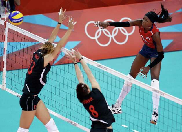 United States' Destinee Hooker, right, spikes the ball over Turkey's Neriman Ozsoy, left, and Bahar Toksoy, center, during a women's preliminary volleyball match at the 2012 Summer Olympics, Sunday, Aug. 5, 2012, in London. Photo: Jeff Roberson, Associated Press / AP
