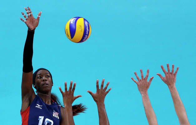 United States' Destinee Hooker, left, spikes the ball over defenders from Brazil during a women's gold medal volleyball match at the 2012 Summer Olympics, Saturday, Aug. 11, 2012, in London. Photo: Jeff Roberson, Associated Press / AP