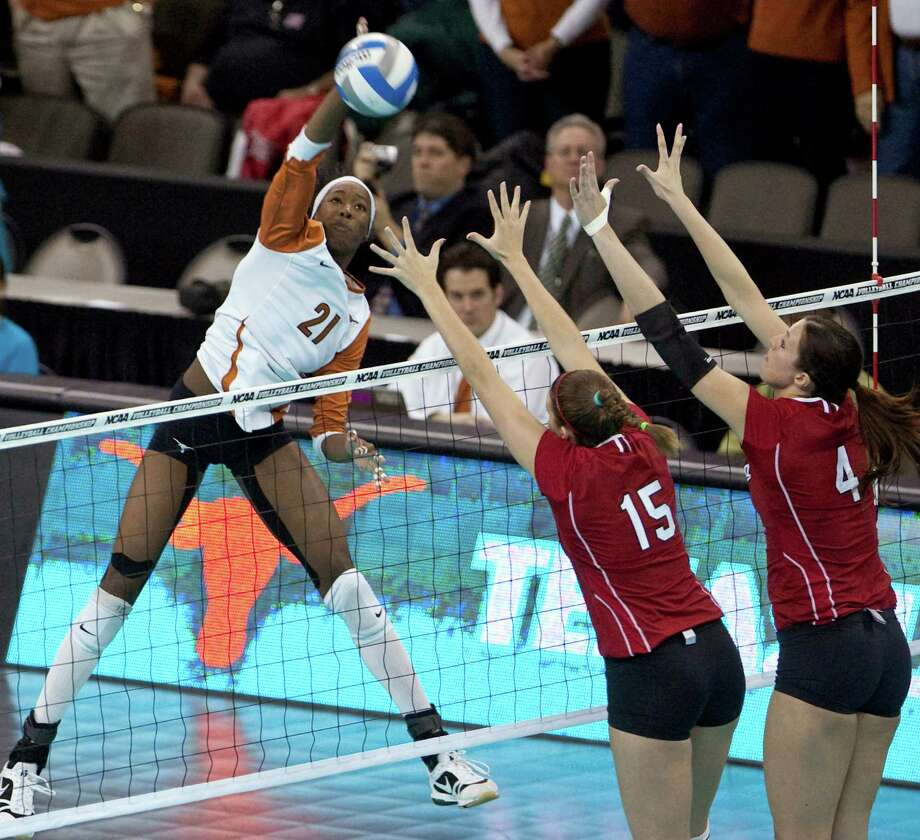 Texas' Destinee Hooker (21) goes for a kill against Nebraska's Kori Cooper (15) and Lindsey Licht, right, in the NCAA college volleyball Omaha regional final match in Omaha, Neb., Saturday, Dec. 12, 2009. Photo: Nati Harnik, Associated Press / AP