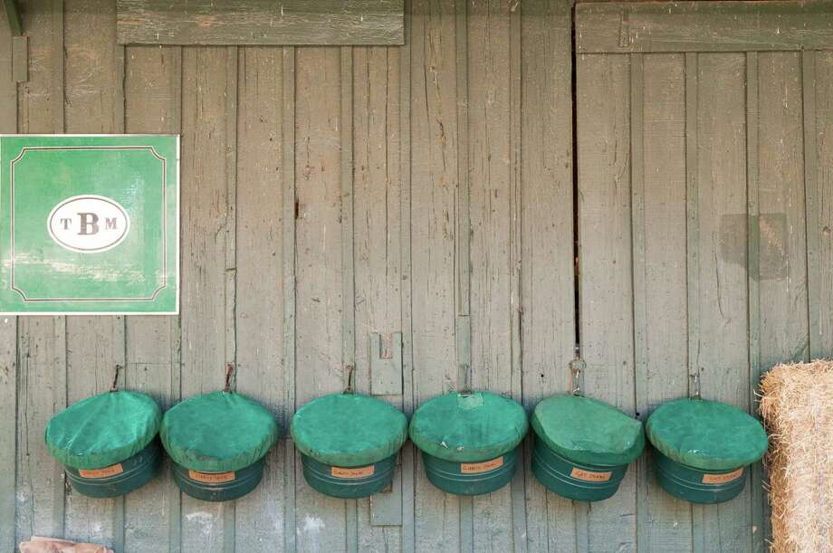 "Phil Olivo of Saratoga, another winner in our recently ended Saratoga Track Pics contest, features the feed buckets for thoroughbreds lined up along a barn wall. ""I was fortunate to be 'back stretch' at the Saratoga Race Track and wanted a photo that shows another side of racing and the race horses,"" Olivo says. ?This composition of feed buckets, each with a horse?s name,  with the stable as the background caught my eye."" (Phil Olivo)"