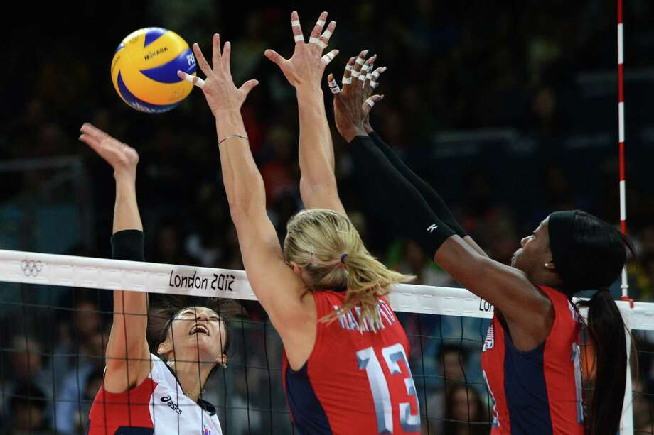South Korea's Han Song-Yi (L) spikes as US players Destinee Hooker (R) and Christa Harmotto attempt to block during the Women's semifinal volleyball match between South Korea and the US in the 2012 London Olympic Games in London on August 9, 2012. Photo: KIRILL KUDRYAVTSEV, AFP / Getty Images / AFP