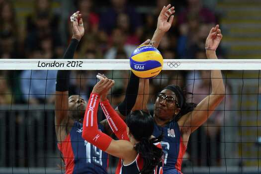Dominican Republic's Milagros Cabral De La Cruz (C) spikes as Destinee Hooker (L) and Foluke Akinradewo of the US attempt to block during the Women's quarterfinal volleyball match between the US and Dominican Republic in the 2012 London Olympic Games in London on August 7, 2012. Photo: KIRILL KUDRYAVTSEV, AFP / Getty Images / AFP