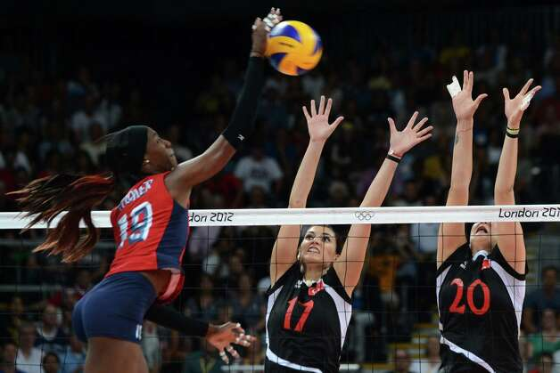 US player Destinee Hooker (L) spikes as Turkey's Naz Aydemir (C) and Busra Cansu attempt to block during the Women's preliminary pool B volleyball match between the US and Turkey in the 2012 London Olympic Games in London on August 5, 2012. Photo: KIRILL KUDRYAVTSEV, AFP / Getty Images / AFP