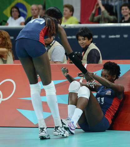 US Destinee Hooker (L) helps teammate Megan Hodge to stand up during the women's volleyball gold medal match of the London 2012 Olympics Games against Brasil, in London on August 11, 2012. Photo: MANAN VATSYAYANA, AFP / Getty Images / AFP