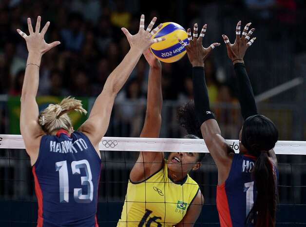 Brazil's Fernanda Rodrigues (C) tries to spike the ball past US Christa Harmotto (L) and Destinee Hooker during the women's volleyball gold medal match of the London 2012 Olympics Games, in London on August 11, 2012. Photo: MANAN VATSYAYANA, AFP / Getty Images / AFP