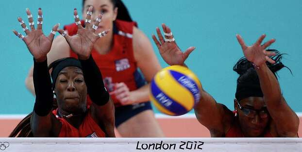 Destinee Hooker (L) and Foluke Akinradewo (R) of the US block a shot  during their Women's semi-final volleyball match against South Korea in the London 2012 Olympic Games at the Earl's Court Arena in London on August 9, 2012. USA beat South Korea 25-20, 25-22, 25-22. Photo: MANAN VATSYAYANA, AFP / Getty Images / AFP