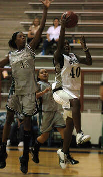Clark's Sanetra Jackson (40) breezes past Southwest's Destinee Hooker (33) toward the basket during their season opening basketball game at O'Connor High School on Tuesday, November 9, 2004. Photo: KIN MAN HUI, San Antonio Express-News / SAN ANTONIO EXPRESS-NEWS