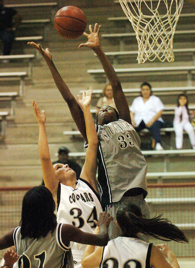 Southwest's Destinee Hooker (33) skies above Clarks' Liz Purnell (34) for a rebound during their basketball game at O'Connor High School on Tuesday, November 9, 2004. Southwest defeated Clark, 58-46. Photo: KIN MAN HUI, San Antonio Express-News / SAN ANTONIO EXPRESS-NEWS
