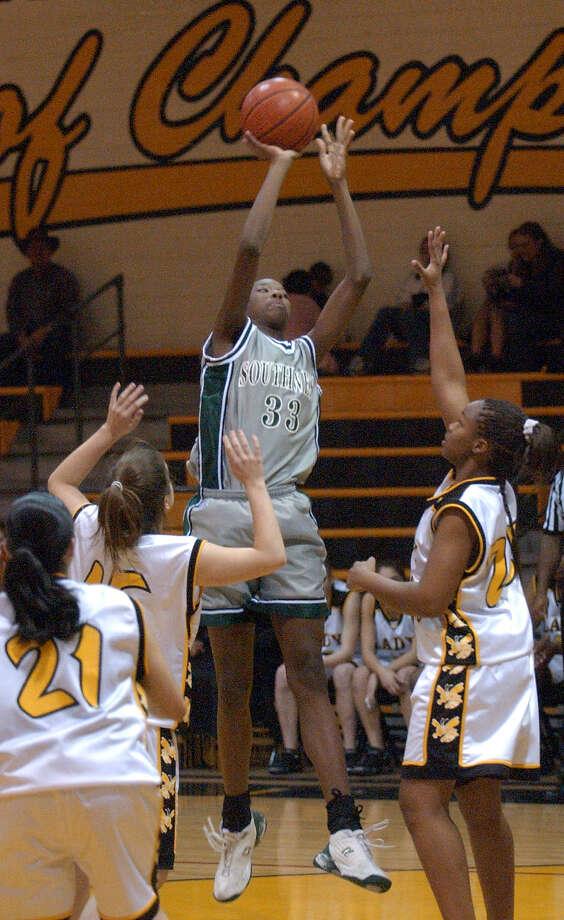 Southwest High School's Destinee Hooker (33) puts up a shot over East Central's Regina Sosa (21), Juie Bain (15) and Tylisha Nails (31) during girls high school basketball action on Tuesday, Feb. 10, 2004. Photo: BILLY CALZADA, San Antonio Express-News