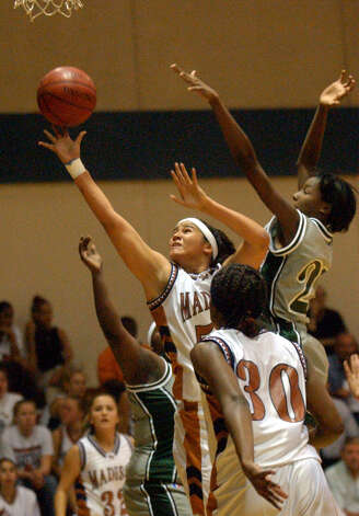 Madison High's Amanda Espinoza goes for a layup as Southwest's Destinee Hooker attempts to defend during girls basketball on Tuesday, Nov. 19, 2002. Photo: BILLY CALZADA, San Antonio Express-News / SAN ANTONIO EXPRESS-NEWS