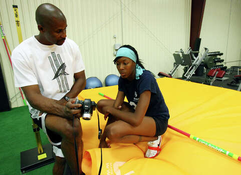 "Charles Austin (left), owner of So High Sports & Fitness Training and 1996 Olympic High Jump Gold Medalist and record holder (7'10""), and Destinee Hooker, who is trying to make the Olympic team in the high jump, shows Destinee Hooker a video of her practice June 24, 2008 at So High Sports & Fitness Training in San Marcos. Photo: EDWARD A. ORNELAS, San Antonio Express-News / eornelas@express-news.net"