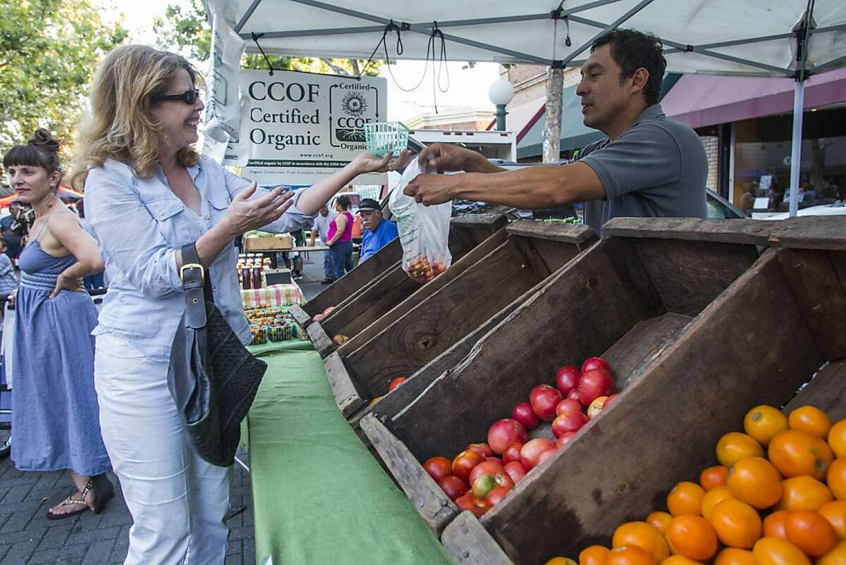 Carolin Husting from San Francisco Buying some Baby Tomatoes from Organic Farmer Luis E Miranda at the Farmers Market, in Lodi, California, on thursday August 30th 2012 By Ken James/SPECIAL TO THE CHRONICLE