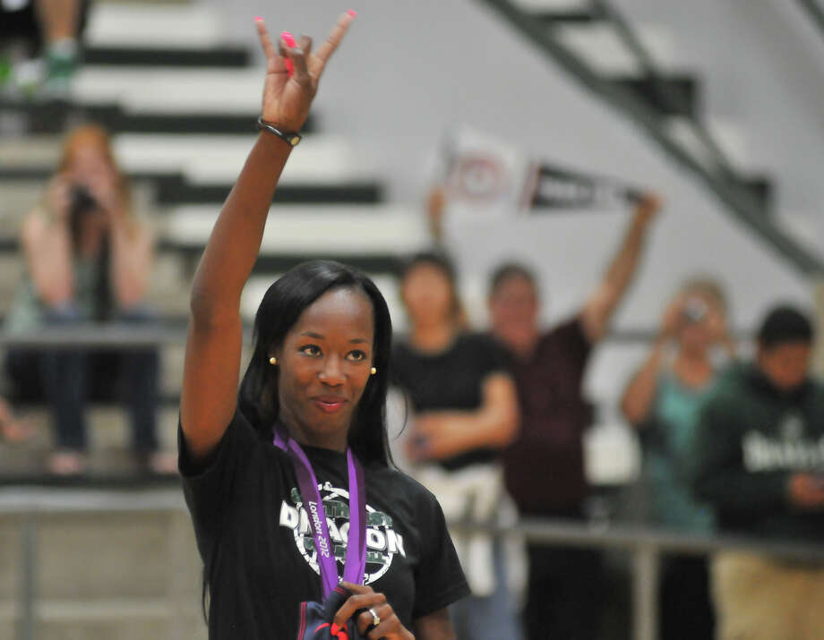 "Olympic volleyball silver medalist and Southwest graduate Destinee Hooker gives the ""Hook 'Em Horns"" signal to the crowd during a ceremony Tuesday evening, Sept. 4, 2012, that retired her jersey number from the school's volleyball team. Photo: ROBIN JERSTAD, For The Express-News"