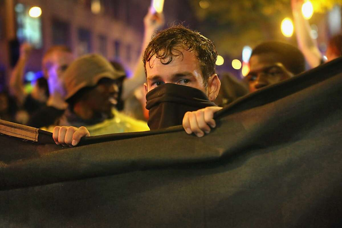 CHARLOTTE, NC - SEPTEMBER 04: A protestor shields himself with a tarp during a march on the Democratic National Convention September 4, 2012 in Charlotte, North Carolina. Police officers from around the country are in Charlotte to provide security for the Democratic National Convention which begins today and runs through Thursday. (Photo by Scott Olson/Getty Images)