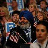 A delegate holds a U.S. flag at the Democratic National Convention (DNC) in Charlotte, North Carolina, U.S., on Tuesday, Sept. 4, 2012. San Antonio Mayor Julian Castro, a Stanford University and Harvard Law School graduate, has the role of first Hispanic keynote speaker at the Democratic National Convention. Photographer: Daniel Acker/Bloomberg