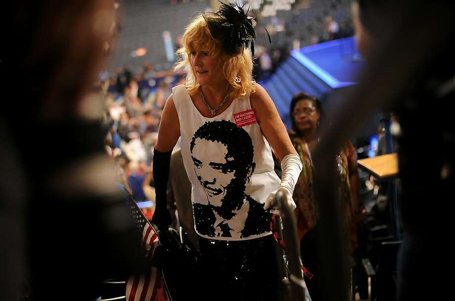 Kelly Jacobs, a delegate from Mississippi, wears a shiny Obama dress while walking up stairs before the start of day one at the Democratic National Convention (DNC) in Charlotte, North Carolina, U.S., on Tuesday, Sept. 4, 2012. San Antonio Mayor Julian Castro, a Stanford University and Harvard Law School graduate, has the role of first Hispanic keynote speaker at the Democratic National Convention. Photo: Daniel Acker, Bloomberg