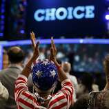 A delegate wearing a U.S. flag hat applauds at the Democratic National Convention (DNC) in Charlotte, North Carolina, U.S., on Tuesday, Sept. 4, 2012. San Antonio Mayor Julian Castro, a Stanford University and Harvard Law School graduate, has the role of first Hispanic keynote speaker at the Democratic National Convention. Photographer: Victor J. Blue/Bloomberg