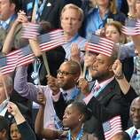 Supporters wave flags at the Time Warner Cable Arena in Charlotte, North Carolina, on September 4, 2012 on the first day of the Democratic National Convention (DNC). The DNC is expected to nominate US President Barack Obama to run for a second term as president. AFP PHOTO  Stan HONDASTAN HONDA/AFP/GettyImages