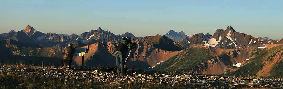 In this stitched image, Jim Wickwire, at left, and Jim Davis look out over the North Cascades that includes the North Cascades National Park and land that would be included in the expansion of the park. They are standing on the Slate Peak Lookout at 7,400 elevation. (Steve Ringman/Seattle Times/MCT) Photo: Steve Ringman, McClatchy-Tribune News Service