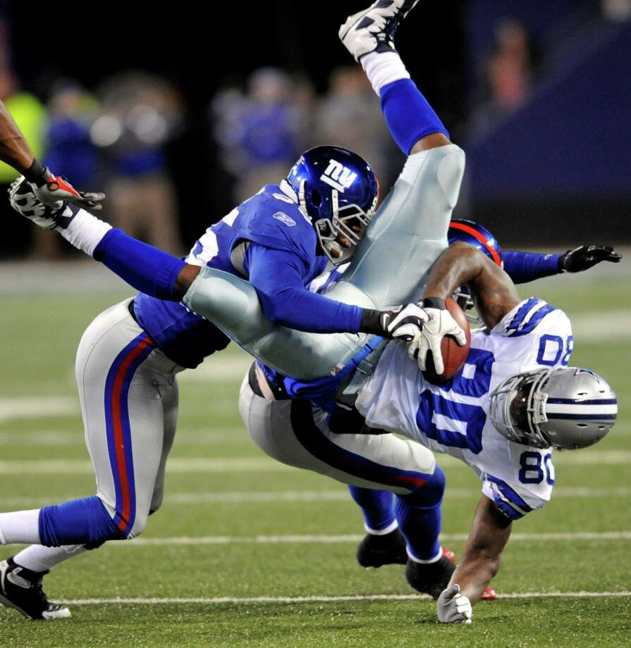Dallas Cowboys wide receiver Martellus Bennett, right, is tackled by New York Giants linebacker Danny Clark, left, and others during the third quarter of an NFL football game Sunday, Nov. 2, 2008, at Giants Stadium in East Rutherford, N.J. The Giants beat the Cowboys 35-14. Photo: Bill Kostroun, Associated Press / FR51951 AP