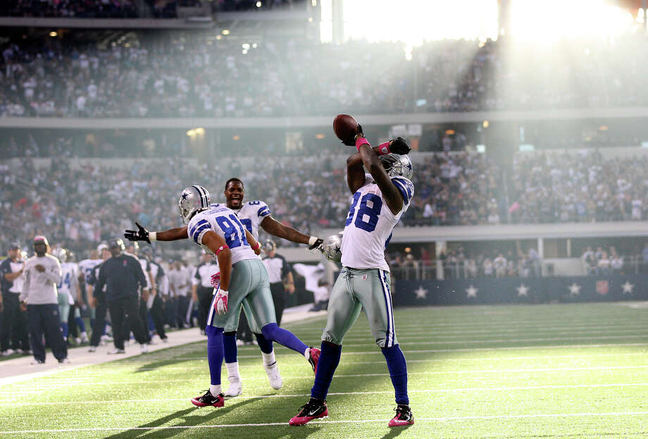 Dallas Cowboys wide receiver Dez Bryant, (88), celebrates a fourth quarter touchdown along with teammates wide receiver Laurent Robinson, (81), and tight end Martellus Bennett in their game against the St. Louis Rams at Cowboys Stadium in Arlington, Sunday, Oct. 23, 2011. Photo: JERRY LARA, San Antonio Express-News / SAN ANTONIO EXPRESS-NEWS