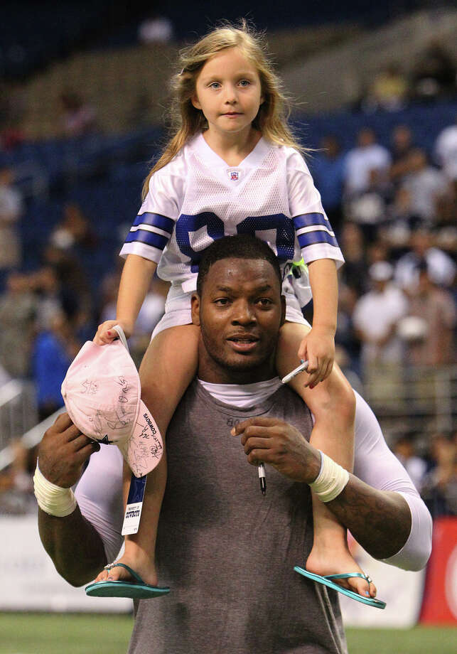 Maya Friedman, 6, of Sugarland rides on the shoulders of Cowboys tight end Martellus Bennett as they went around the field gathering autographs at the end of the afternoon session of the Dallas Cowboys training camp at the Alamodome on Wednesday, Aug. 3, 2011. Photo: KIN MAN HUI, San Antonio Express-News / SAN ANTONIO EXPRESS-NEWS