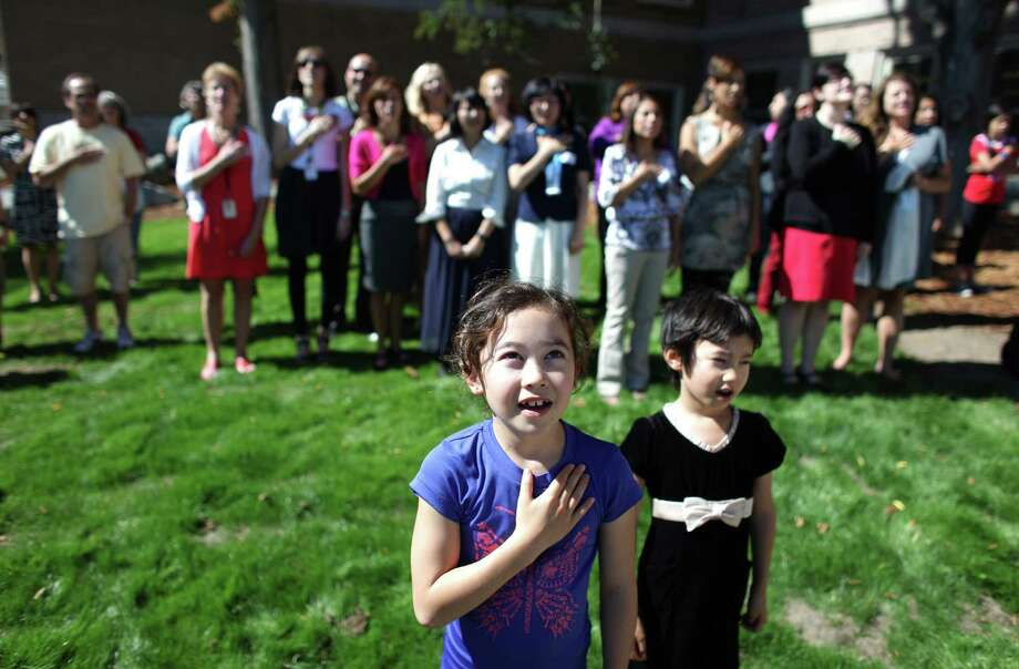 Abbey Amemiya, 9, and her sister Kelsey Amemiya, 6, say the Pledge of Allegiance during the grand opening of the new McDonald International Elementary School. Photo: JOSHUA TRUJILLO / SEATTLEPI.COM