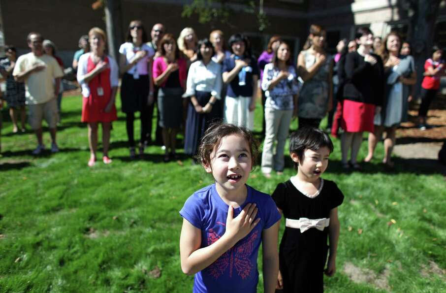 Abbey Amemiya, 9, and her sister Kelsey Amemiya, 6, say the Pledge of Allegiance during the grand op