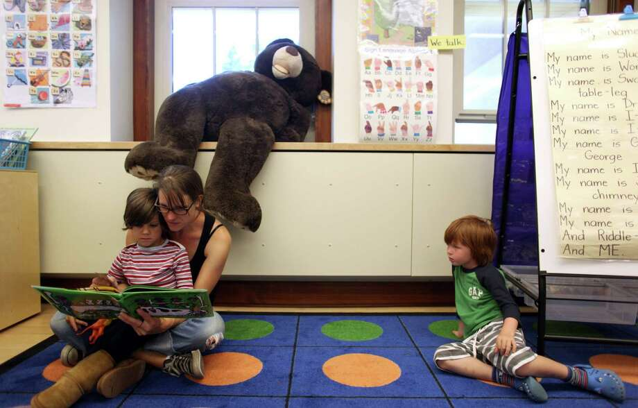 Amy Neil reads to her son Cannon, 5, who is starting kindergarten, as classmate Charlie McManus, 5, looks on. The kids were welcomed during the grand opening of the new McDonald International Elementary School. Photo: JOSHUA TRUJILLO / SEATTLEPI.COM