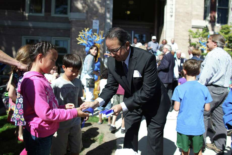 New Seattle Public Schools Superintendent José Banda hands out pieces of ribbon after cutting it during the grand opening of the new McDonald International Elementary School in Seattle's Wallingford neighborhood. Photo: JOSHUA TRUJILLO / SEATTLEPI.COM