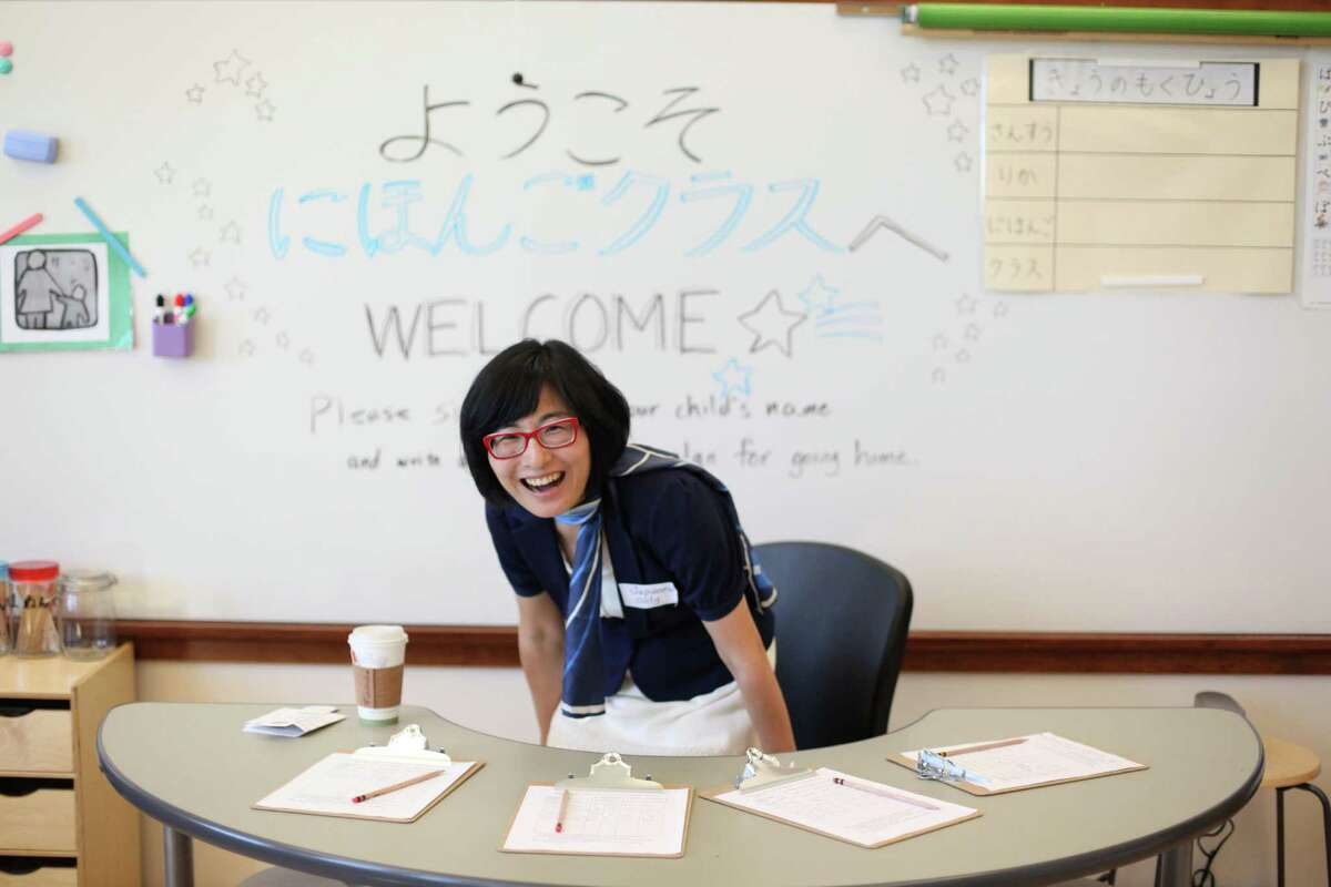 First grade assistant Keiko Ishikawa takes a seat during the grand opening of the new McDonald International Elementary School.