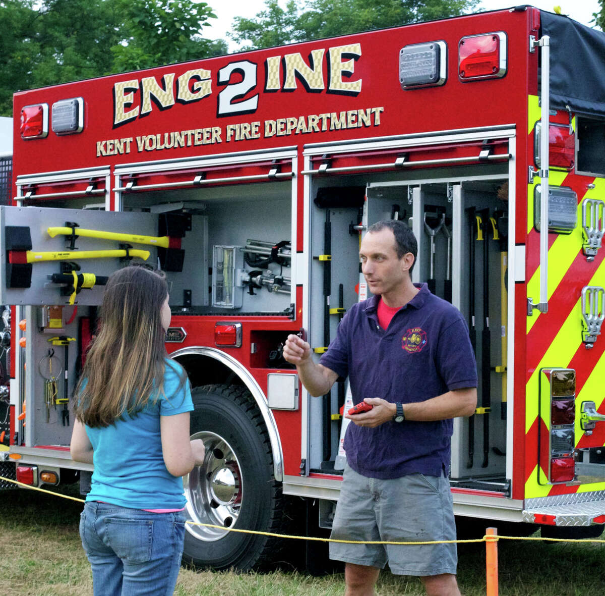 John Russell of the Kent Volunteer Fire Departmentfields questions from Jennifer Petrone, 14, of Kent during the Kent Firemen's Fair and Parade, Aug. 23-25, 2012.