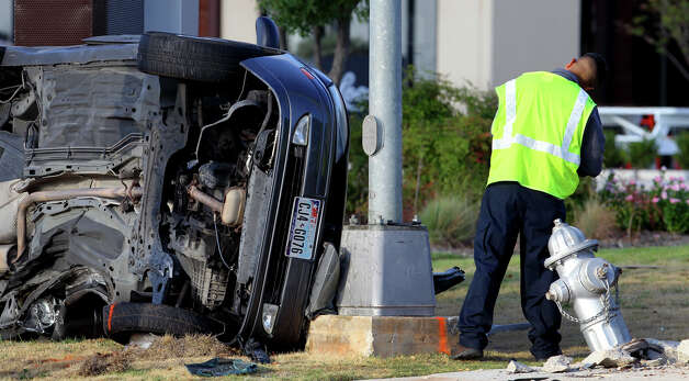 A wrecker driver works Wednesday morning September 5, 2012 at the scene of a fatal traffic accident at the corner of Sigma and Sonterra. Detective Art Knox said a 19-year-old male was traveling east on the 700 block of Sonterra when he lost control of his Ford Focus shortly before 6:00 a.m. and struck a fire hydrant. Knox said the driver may have over corrected once having lost control of the vehicle. The man died at the scene. Photo: John Davenport, San Antonio Express-News / San Antonio Express-News