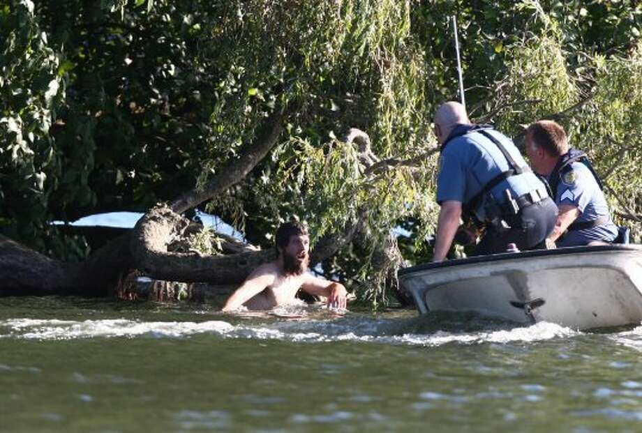 Officers pursue a naked man around Duck Island after they said he assaulted two teenagers at Green Lake Park and was chased into the middle of Green Lake. He clung naked to a buoy before swimming to Duck Island where he continued to evade police for about 2 hours. They finally arrested the man.  (JOSHUA TRUJILLO / SEATTLEPI.COM)
