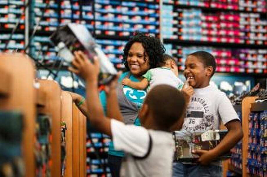 Single mother of three Tameka Morris helps sons Tyler, 6, and Taylor, 9, shop for new shoes at an outlet store in Houston. (HC)
