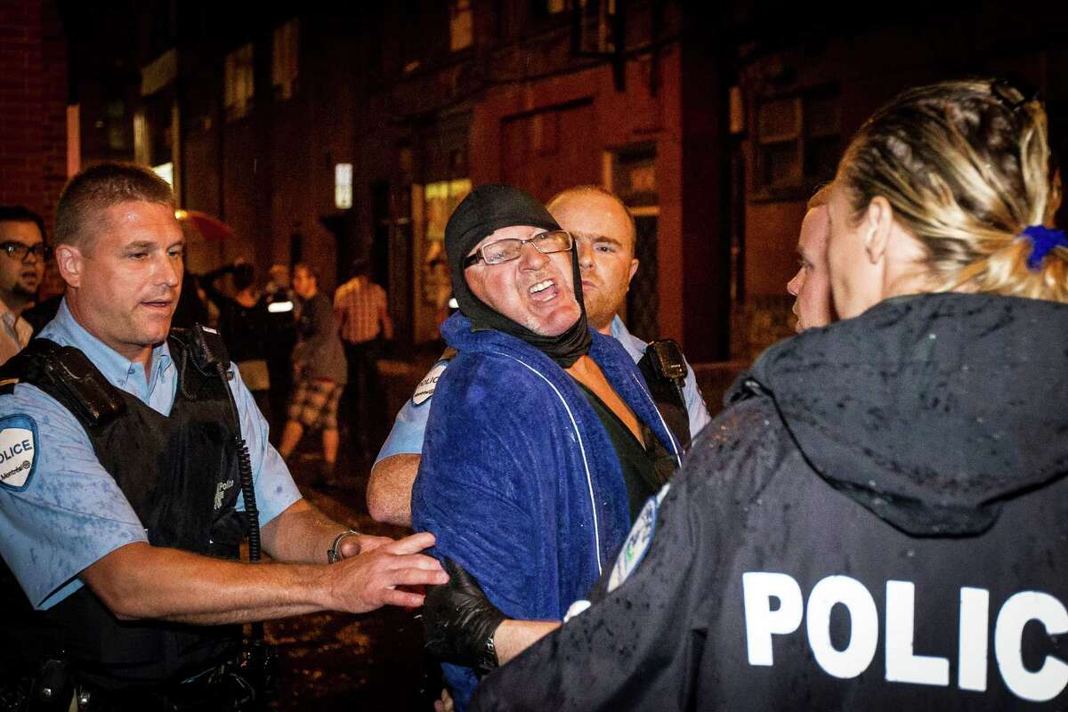 A man is arrested by police outside the Parti Quebecois victory rally in Montreal on Wednesday, Sept. 5, 2012. A masked gunman wearing a blue bathrobe opened fire during a midnight victory rally for Quebec's new premier, killing one person and wounding another. The new premier, Pauline Marois of the separatist Parti Quebecois, was whisked off the stage by guards while giving her speech and uninjured. It was not clear if the gunman was trying to shoot Marois, whose party favors separation for the French-speaking province from Canada. Police identified the gunman only as a 62-year-old man, and were still questioning him Wednesday morning.