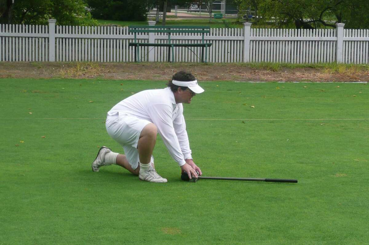 Chris Glowacki uses his mallet to line up a shot at the Greenwich Croquet Club court in Bruce Park