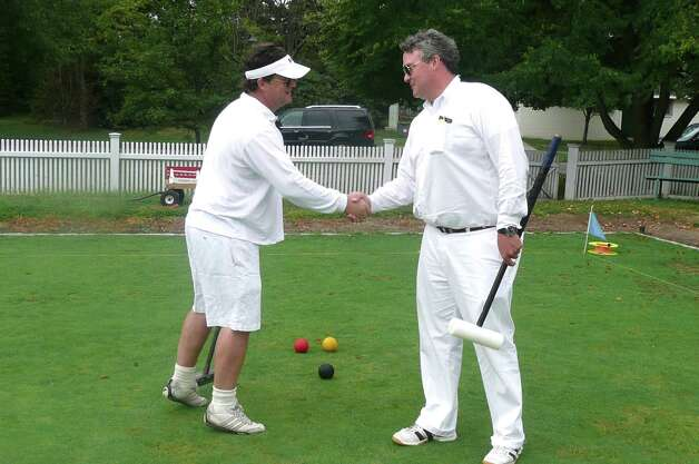 "Traditionally, Chris Glowacki, left, and Chris Fey begin their croquet matches with the toss of a coin to see who starts first, then a hand shake followed by a ""Good luck."" Then, it's down to business. Photo: Anne W. Semmes"
